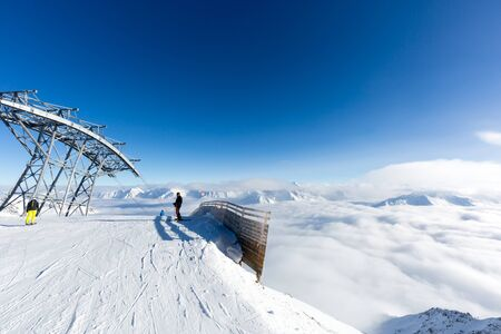 ski lift: Two skiers at the top of a ski lift station in the mountains on a winter day.