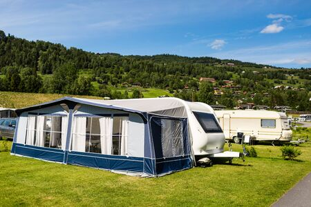 accommodations: Modern caravan with caravan tent at campsite in Norway on a sunny summer day.