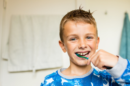 young boy smiling: Close-up of young boy brushing his teeth with toothbrush while standing in bathroom with natural daylight. Stock Photo