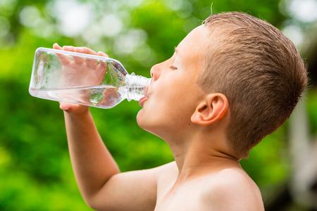 Vértes fiatal fiú ivóvíz tiszta csapvíz átlátszó műanyag kulacs, miközben a szabadban egy forró nyári napon.