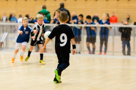 northern european: Young northern european boys playing a indoors soccer training match inside an indoor sports arena.