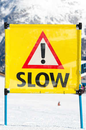 ski run: Yellow warning sign with the text slow and exclamation mark placed on ski run at ski resort. Stock Photo