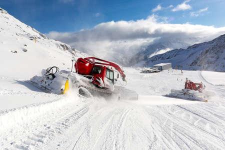 snowcat: Trailing groomer grooming a ski run at ski resort on a sunny winter day.