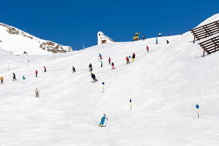 skipiste: Skiers at ski run on a sunny day at the ski resort Soelden in Austria.