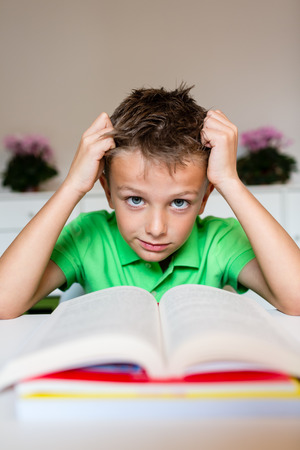 difficulties: Young boy in green polo shirt having serious learning difficulties while trying to read a textbook from school.