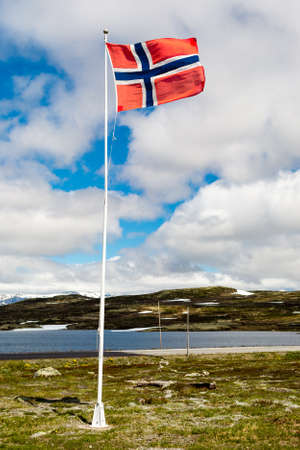western part: Norwegian flag on flagpole near the famous Hardangervidda plateau in western part of Norway. Stock Photo