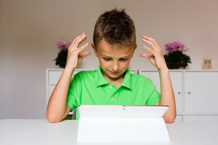 perplex: Young boy sitting at table and showing his frustration while using his white tablet.
