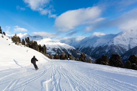 Male skier skiing on easy ski piste on a sunny winter day.