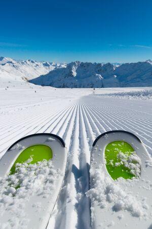Paire de nouveaux skis debout sur la neige fraîche sur les pistes de ski nouvellement soigné à la station de ski sur une journée d'hiver ensoleillée.