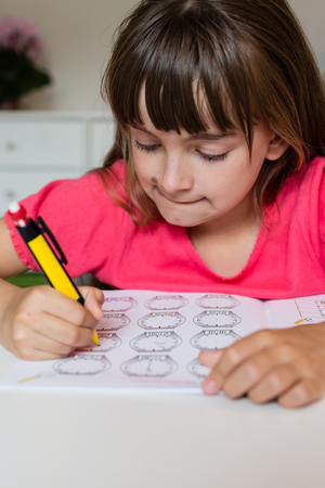 learning by doing: Young white girl writing with her pencil and doing her elementary school homework while sitting at white table. Stock Photo