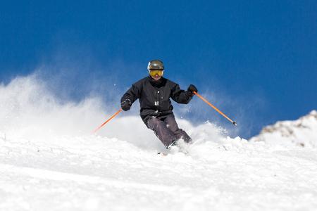 skiing: Male skier skiing in fresh snow on ski slope on a sunny winter day at the ski resort Soelden in Austria.