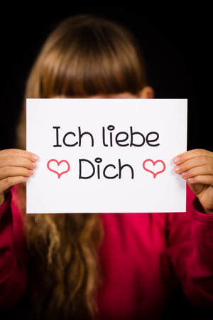 first love: Studio shot of child holding a sign with German words Ich liebe Dich - I Love You