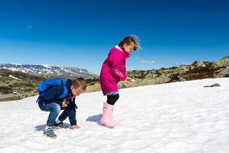 having fun in the snow: Two young kids having fun with snow on their summer vacation to hardangervidda in Norway.