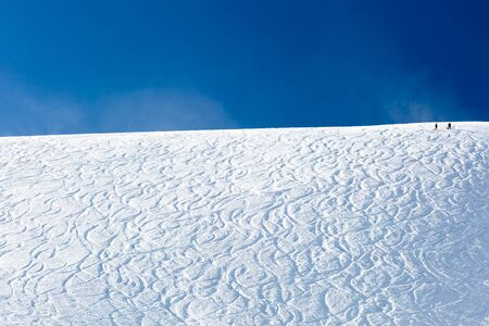 offpiste: Off piste ski tracks on powder snow on a sunny winter day with blue sky. Stock Photo