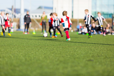 enfant qui joue: Flou de jeunes enfants jouant un match d'entra�nement de football en plein air sur un terrain de soccer synth�tique. Banque d'images
