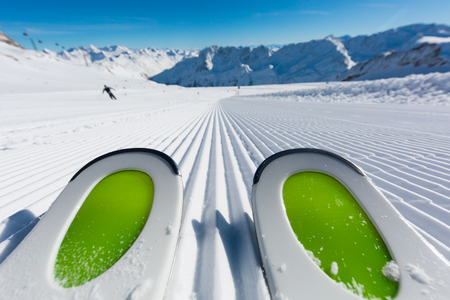 Pair of new skis standing on the fresh snow on newly groomed ski slope at ski resort on a sunny winter day. Archivio Fotografico