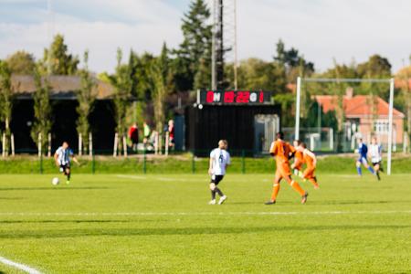 Ondiepe scherptediepte schot van groep mannelijke voetballers spelen amateur voetbalwedstrijd op zonnige zomerdag op eenvoudige sport-locatie in Denemarken. Stockfoto