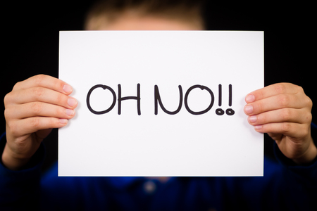 no mistake: Studio shot of child holding an Oh No sign made of white paper with handwriting. Stock Photo