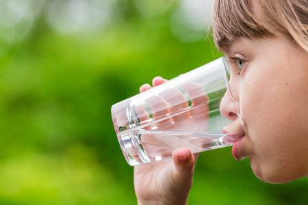 Close-up of young scandinavian child drinking fresh and pure tap water from glass with a blurred green background. Archivio Fotografico