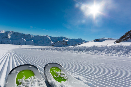 ski run: Pair of ski tips standing on the fresh snow on newly groomed  ski piste at ski resort on a sunny winter day. Stock Photo