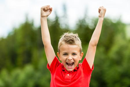 puÑos: Ser niño confiado con el puño en alto celebrando un éxito o la victoria reciente. Foto de archivo