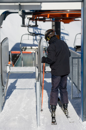 chair lift: Male skier getting ready to board a chair lift at a ski resort. Stock Photo