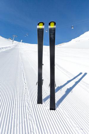 ski run: Pair of modern carving skis standing on newly groomed ski piste.
