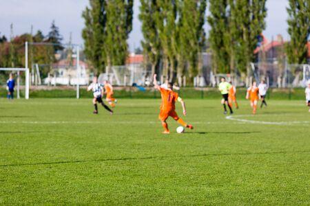 Ondiepe scherptediepte shot van groep mannelijke voetballers amateur voetbalwedstrijd op zonnige zomerdag spelen op eenvoudige sportlocatie in Denemarken.