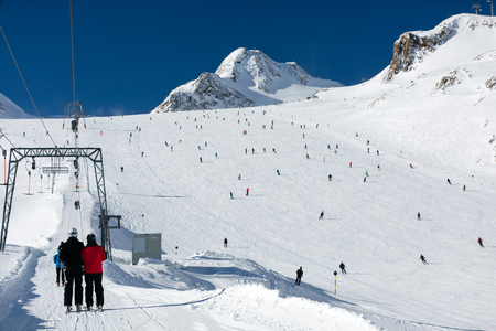 ski run: Scattered groups of skiers descend a wide ski run at the Tiefenbach glacier at the Austrian ski resort Soelden. Stock Photo