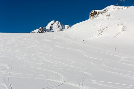 ski run: Fresh ski tracks on ski slope with new white snow at the ski resort Soelden in the Austrian Alps.