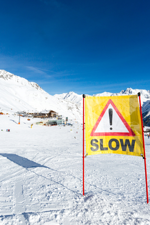 ski run: Yellow slow down warning sign placed in the snow on the piste at the ski resort Soelden in Austria.
