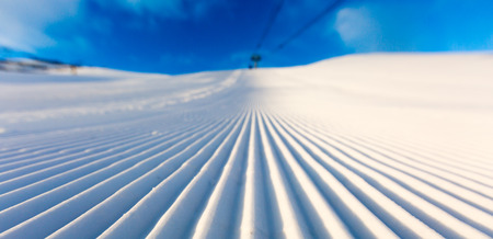 ski track: Newly groomed snow on ski slope at ski resort on a sunny winter day. Stock Photo