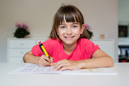 Girl with pencil in her hand and looking at camera while being ready to do her homework.