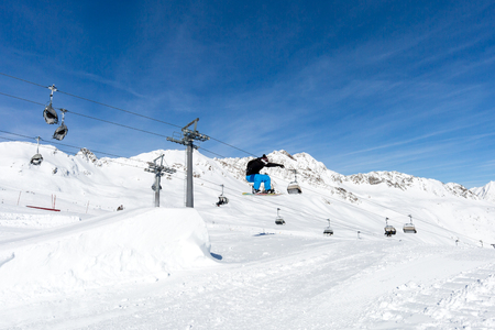 ski run: Male snowboarder performs a jumping trick at the snowpark in Soelden, Austria.