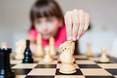 ajedrez: Young white child playing a game of chess on large chess board.