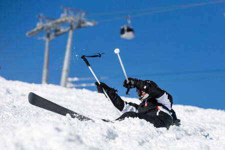 Male skier trying to get back on his skis after crashing in new powder snow.