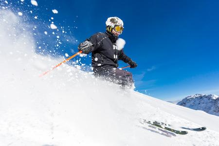 Mannelijke skiër skiën in de verse sneeuw op de piste op een zonnige winterse dag in het skigebied Sölden in Oostenrijk. Stockfoto