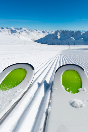 piste: Pair of ski tips standing on the fresh snow on newly groomed  ski piste at ski resort on a sunny winter day. Stock Photo