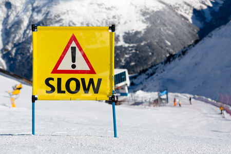 ski run: Yellow warning sign with the text slow and exclamation mark placed on ski piste at ski resort. Stock Photo