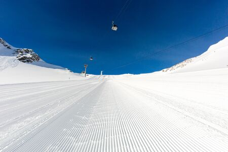 ski track: Fresh snow at recently groomed ski run at ski resort in the Alps on a sunny winter day. Stock Photo