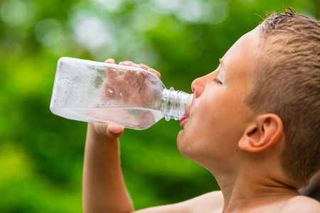 Closeup of young boy drinking fresh and clean cold tap water from transparent plastic drinking bottle while outdoors on a hot summer day.