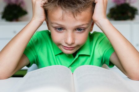 learning by doing: Young boy in green polo shirt having serious learning difficulties while trying to read a textbook from school.