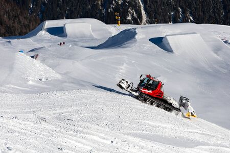 snow grooming machine: Piste machine preparing the snow park at the Austrian ski resort Soelden.