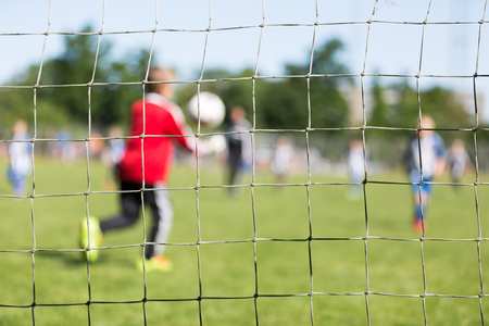 goal keeper: Close-up of soccer goal net with blurred young boy acting as soccer goal keeper on green grass during kids soccer match. Stock Photo