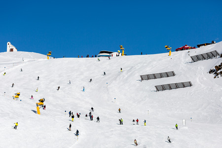 skiers: Groups of skiers scattered across a wide ski slope at a ski resort on a sunny winter day. Stock Photo