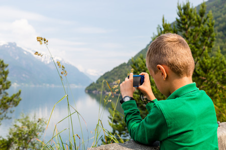 hardangerfjord: Young boy in Norway taking a picture of the surrounding scenery with his compact digital camera.