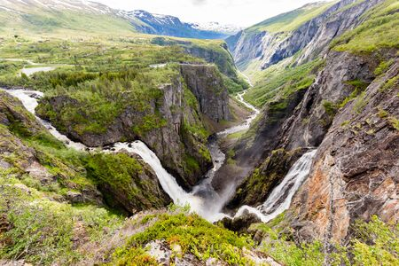 hardangerfjord: The famous Voringsfossen waterfalls near Hardangervidda in Norway is among the most popular tourist attraction during the Norwegian tourism season. Stock Photo