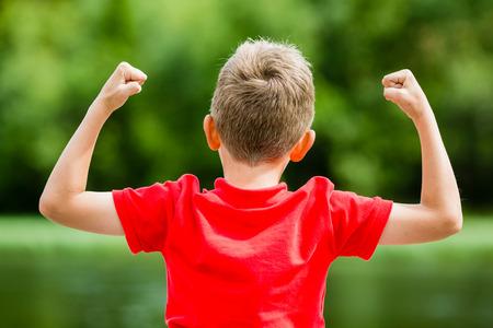 manos levantadas: Muchacho con los brazos y puños en alto en el aire, celebrando el éxito o la victoria.