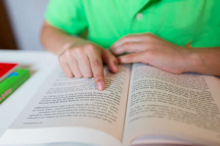 learning by doing: Close-up of young boy reading a text book while sitting at white table.
