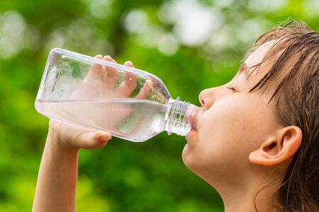 Closeup of young child drinking pure tap water from transparent plastic drinking bottle while outdoors on a hot summer day. Stock Photo